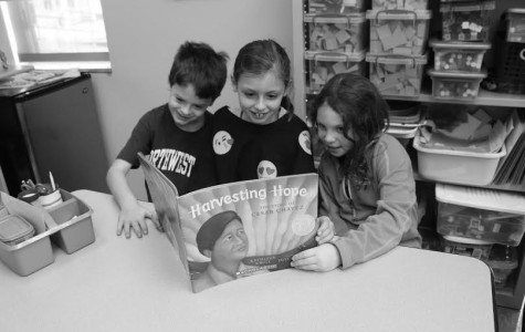 Bill Crouch, Alex Sarnoff, and Kiley Moss in Kathy Davidson's second grade class sit around the table and read