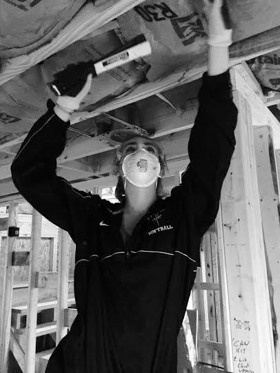 Junior Lauren Murphey installs insulation for a house.