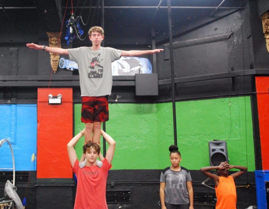 Amateur diabol Aidan Weinberg showcases one of his many circus talents by balancing on one of his peers.