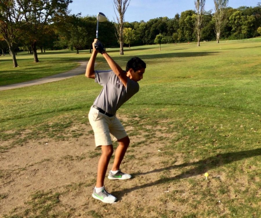 Freshman Rohan Dhingra practices his swing at the driving range before a match.