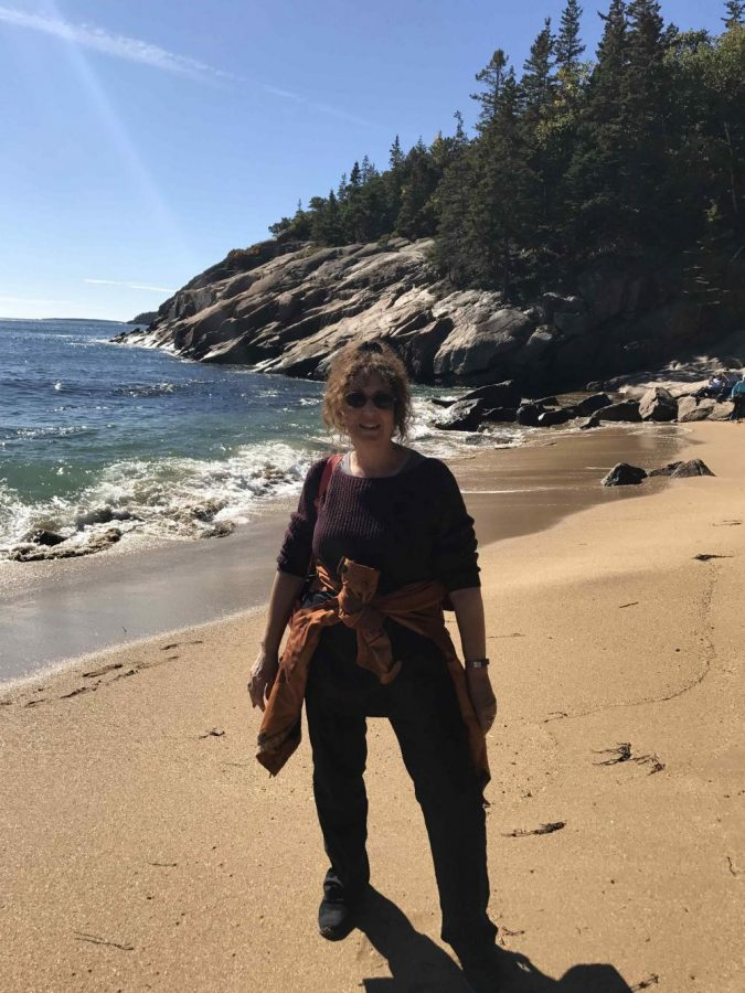 Lorin Pritikin poses for a picture on a beach in Acadia National Park.