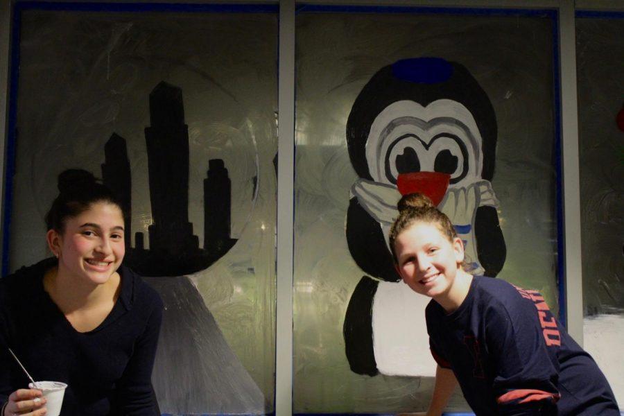 Freshmen Leila Sheridan and Julia Marks stand next to their windows.