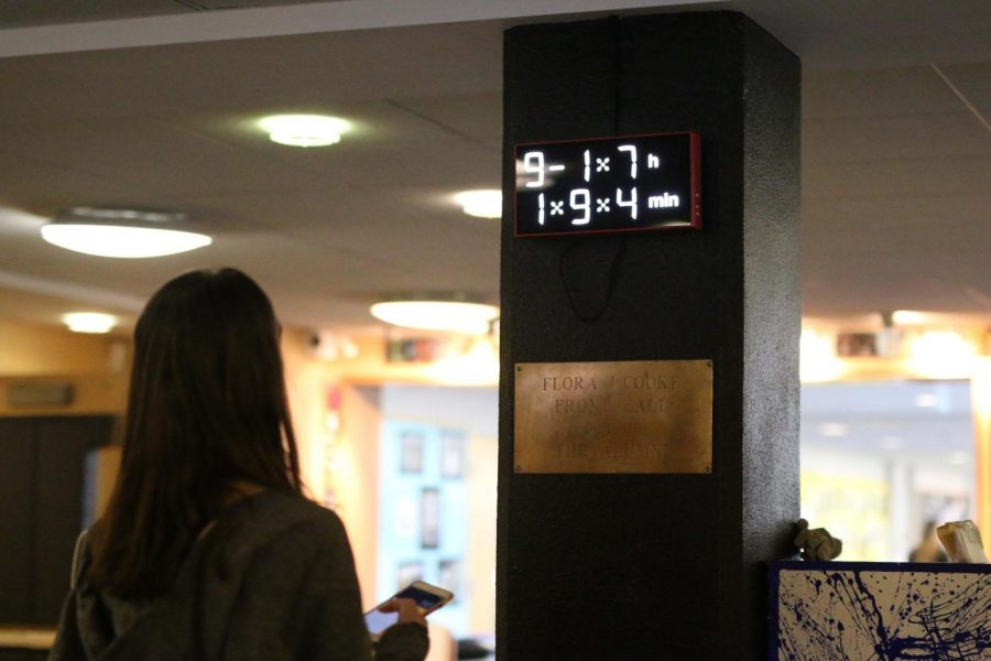 Junior Zoe Laris-Djokovic solves the math clock near the front entrance of the school.