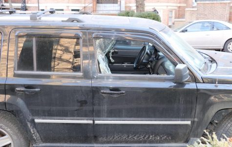 A car with a shattered window parked near Parker after robbery.
