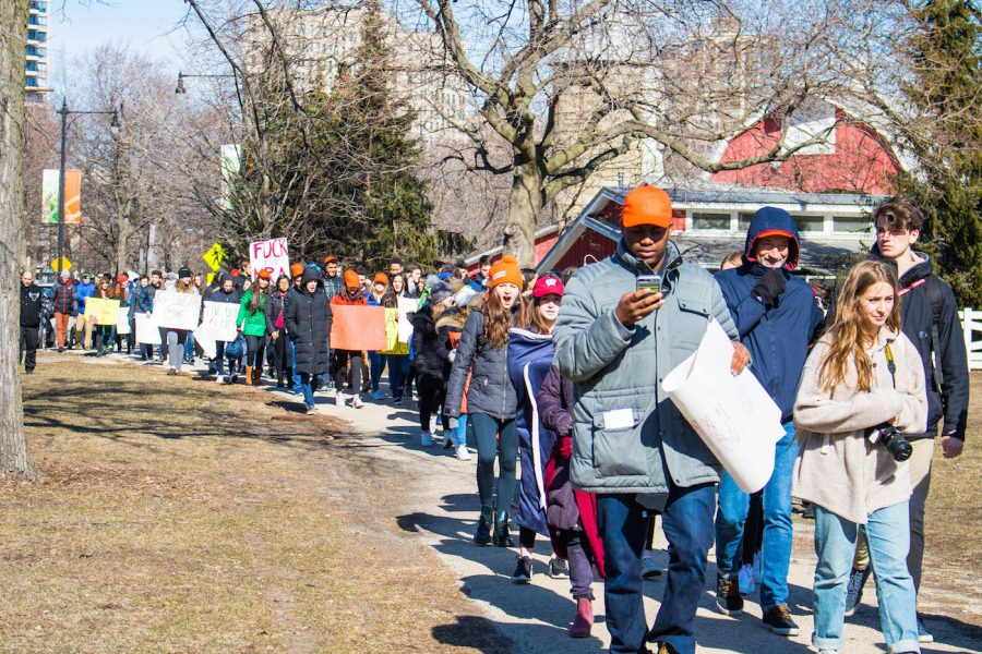 Signs in hand, students march to the rally at South Pond.