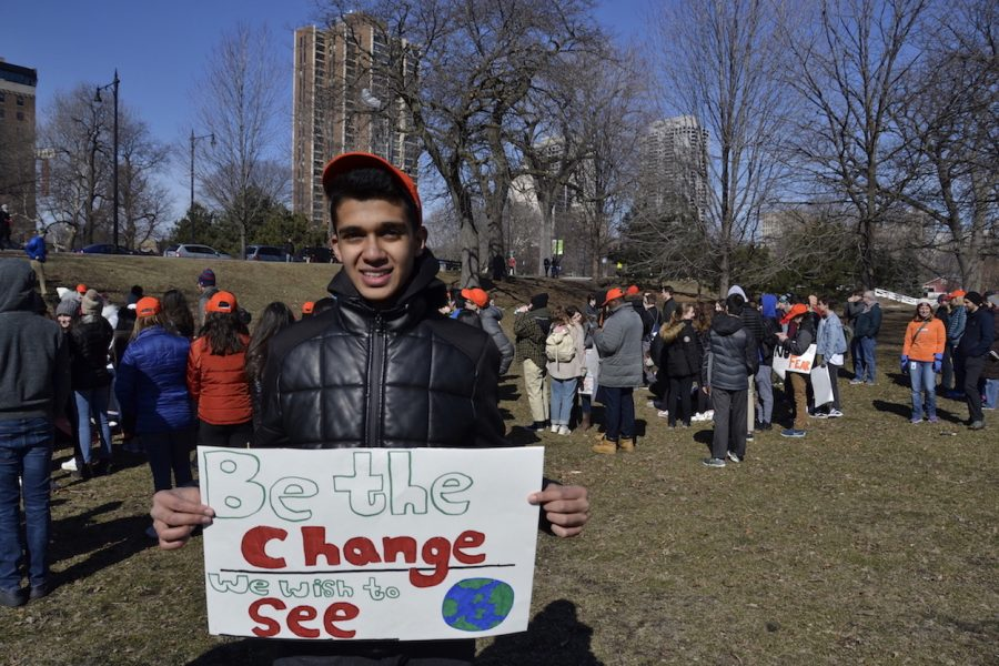 """Sophomore Rohan Jain stands with his sign behind students gathered for the rally. """"I'm marching to provide solidarity to the shooting that happened in Parkland, and trying to prevent gun violence in the future by taking action."""""""