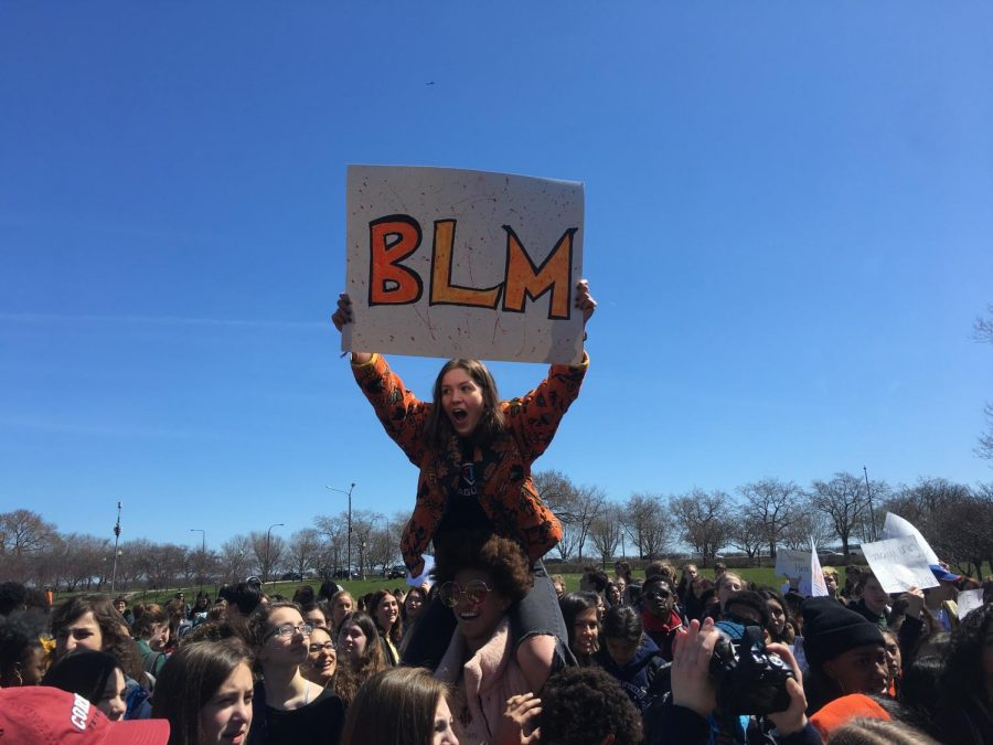 Freshman Nathalie San Fratello holds Black Lives Matter sign while protesting at the Chicago Student Walkout on April 20.