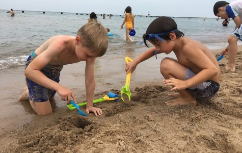 Two boys build sand castles at the beach on a hot day at Parker Summers.