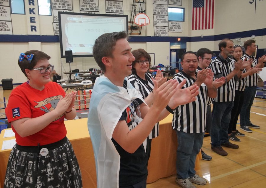 Nathan Satterfield, one of the heads of the upper school's robotics team Robo Theosis, claps at the Chicago Robotics Invitational this summer.