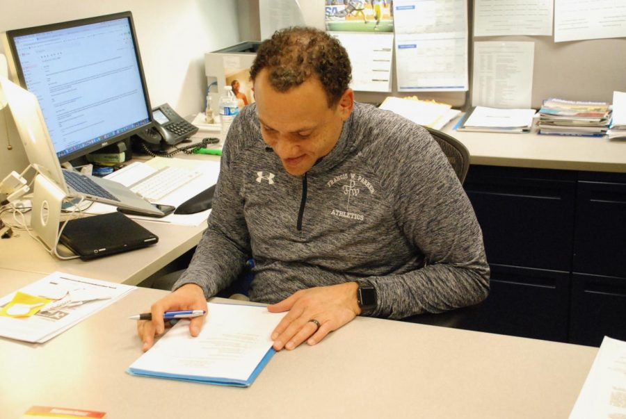 Athletic Director, Bobby Starks, filling out paperwork.