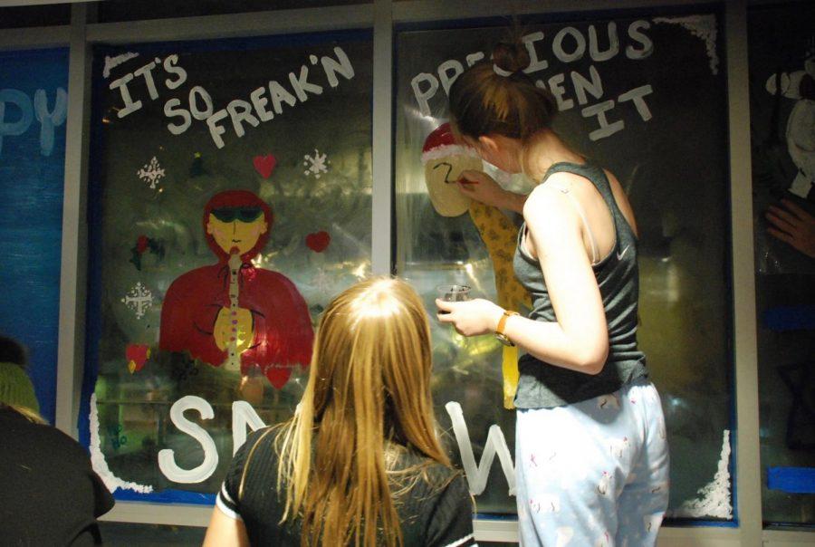 Freshman Katherine Holtz and Ava Utigard painting their windows in the second-floor hallway.