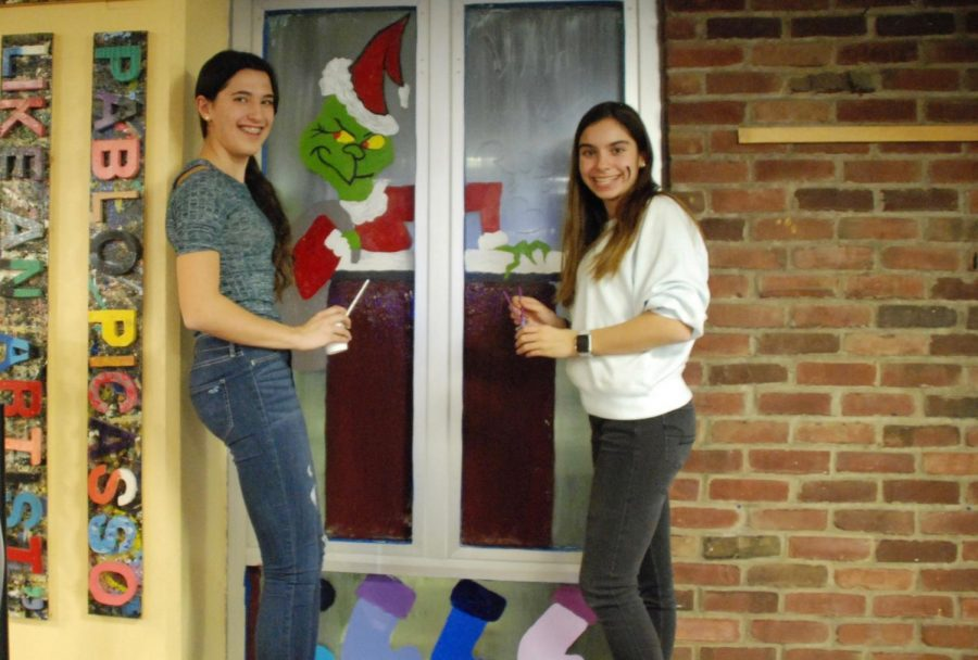 Freshman Alicia Berger and Sophia Rogers painting their windows in the front lobby.