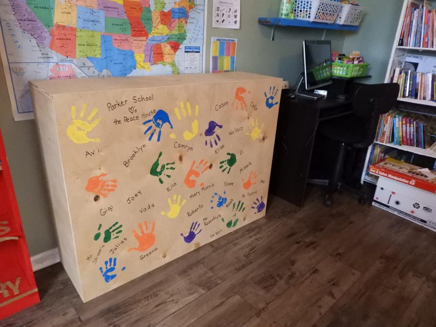 1st-grade students put their handprints on the back of the shelves made for Peace House.