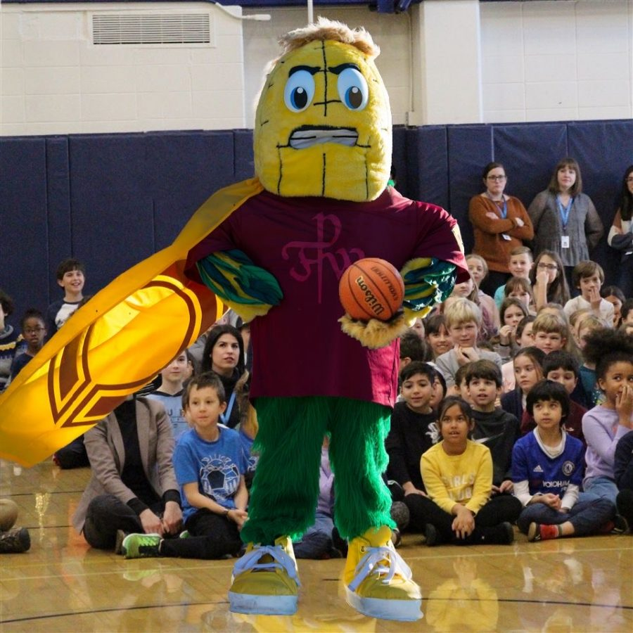 Parker's new mascot, a non-offensive or provoking kernel of corn, triumphantly stands at a pep rally in front of the school.