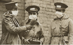 A group of New York train conductors converse while wearing gauze masks during the 1918 flu pandemic. Photo courtesy of the National Archives.